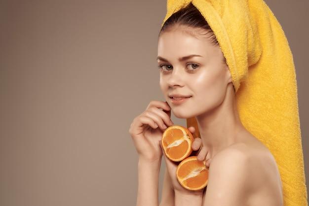 Mulher bonita com tangerina de cuidados da pele de corpo nu na mão. foto de alta qualidade