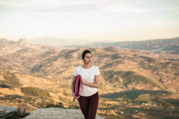 Mulher bonita com tapete de ioga, olhando para longe