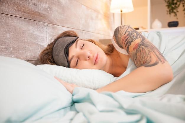 Mulher bonita com tatuagem dormindo na cama em casa com máscara de cobertura.