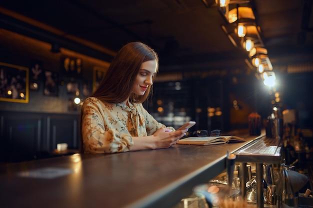 Mulher bonita com telefone móvel, sentado no balcão do bar. uma pessoa feminina em um bar, emoções humanas, atividades de lazer, vida noturna