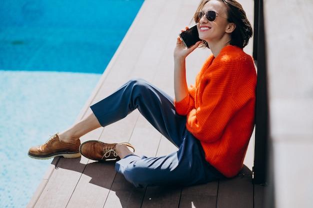 Mulher bonita com telefone sentado à beira da piscina