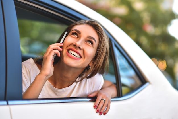 Mulher bonita com telefone sorrindo enquanto está sentado no banco de trás do carro.