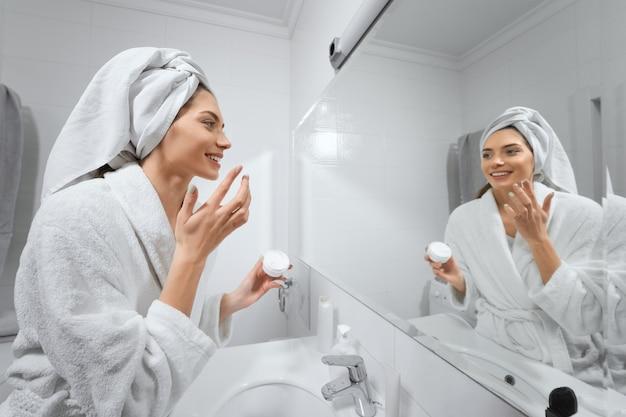 Mulher bonita com toalha branca depois do banho fazendo maquiagem