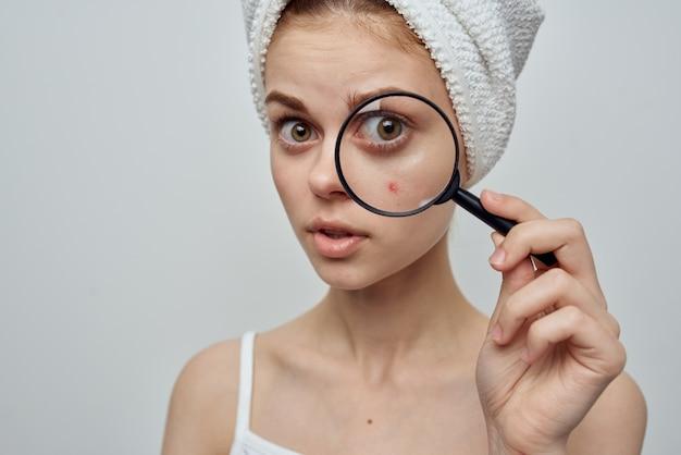 Mulher bonita com toalha na cabeça, lupa para cuidados com a pele perto do rosto
