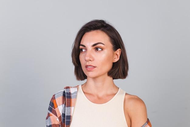 Mulher bonita com top e camisa xadrez na parede cinza com maquiagem, sorriso confiante e positivo, emoções felizes