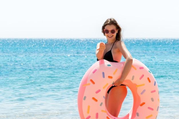 Mulher bonita com um anel de borracha de rosca na praia