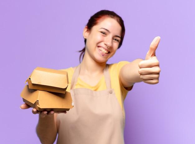 Mulher bonita com um avental. conceito de entrega de hambúrguer para levar