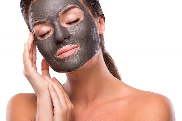 Mulher bonita com um barro ou uma máscara de lama no rosto