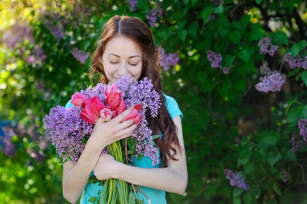 Mulher bonita com um buquê de flores andando no parque primavera