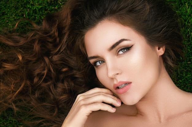 Mulher bonita com um cabelo cacheado saudável está deitado na grama