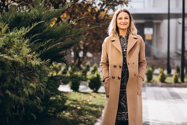 Mulher bonita com um casaco bege fora no parque
