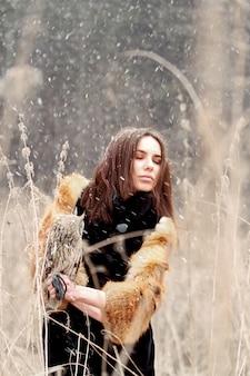Mulher bonita com um casaco de pele com uma coruja na mão