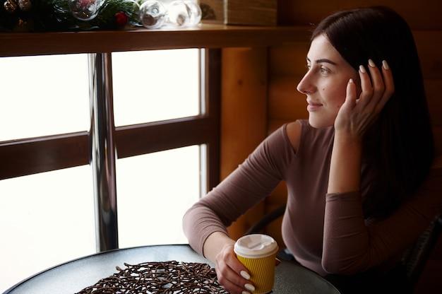 Mulher bonita com um copo de papelão de saborosa bebida quente, sentado no café e olhando pela janela. hora do café