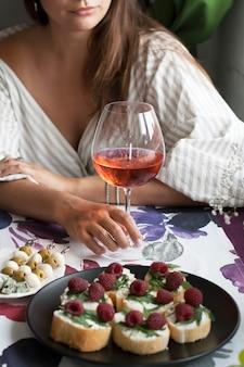 Mulher bonita com um copo de vinho no restaurante, jantar romântico, um prato de fatias de baguete perfumadas com rúcula e framboesa, um prato de canapés de azeitona e mussarela, queijo roquefort.