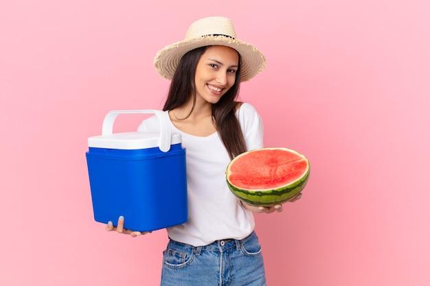 Mulher bonita com um freezer portátil e uma melancia
