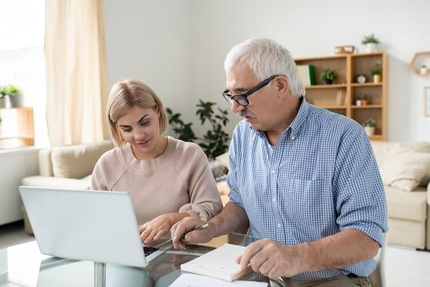 Mulher bonita com um laptop e seu pai aposentado sênior consultando pontos domésticos ou pesquisando dados em casa