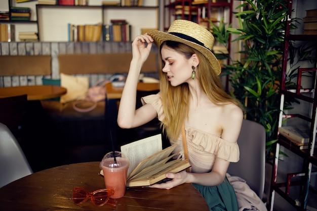 Mulher bonita com um livro nas mãos de uma comunicação de café