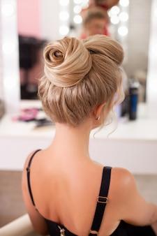 Mulher bonita com um penteado fashion se olhando no espelho no salão de cabeleireiro