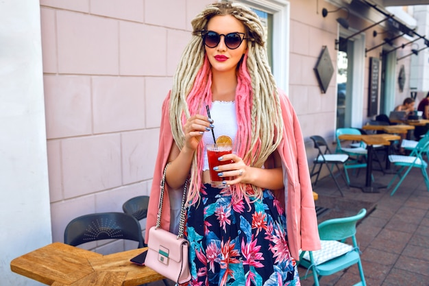 Mulher bonita com um penteado incomum de dreads posando na rua, vestindo um look feminino floral rosa e segurando uma limonada fresca