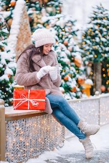 Mulher bonita com um presente perto da árvore de natal na neve ao ar livre em um maravilhoso dia de inverno
