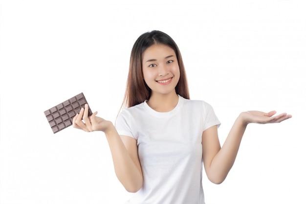 Mulher bonita com um sorriso feliz segurando um chocolate de mão