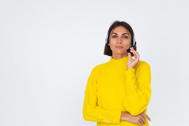 Mulher bonita com um suéter amarelo no gerente branco com fones de ouvido feliz sorriso positivo de boas-vindas