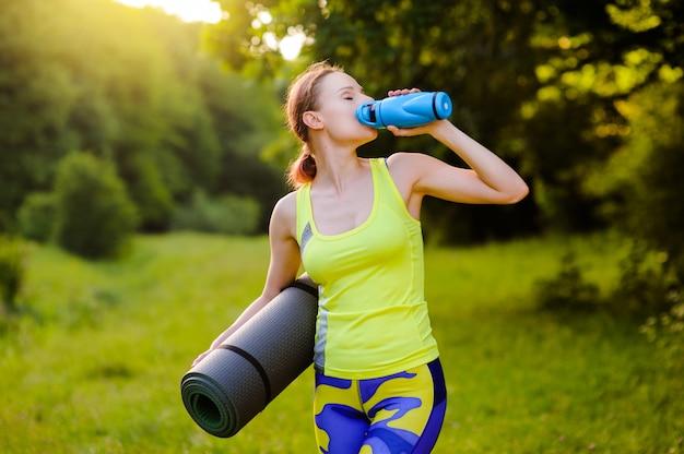 Mulher bonita com um tapete de ioga ao ar livre no parque no pôr do sol