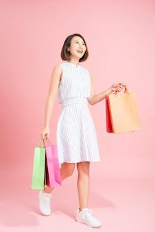 Mulher bonita com um vestido azul claro em um fundo rosa comprando