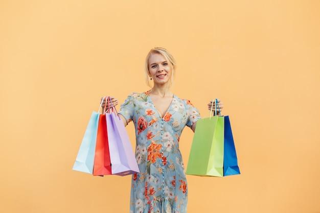 Mulher bonita com um vestido com sacolas de compras em fundo laranja pastel. conceito de compras e vendas de compras