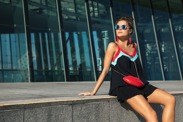 Mulher bonita com uma bolsa estilosa na cidade moderna