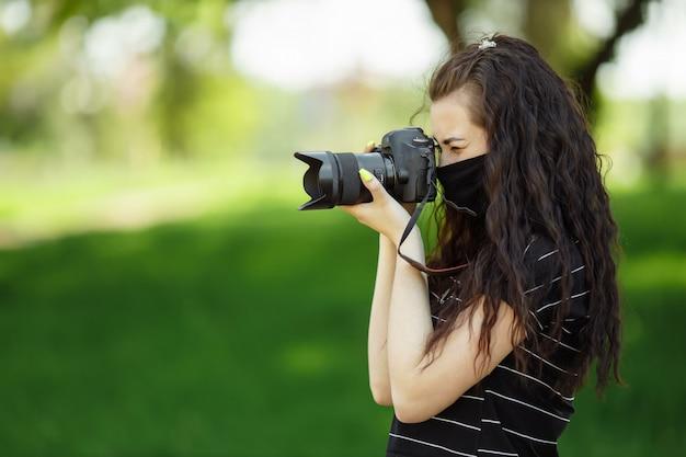 Mulher bonita com uma câmera usa uma máscara médica e tira fotos no parque
