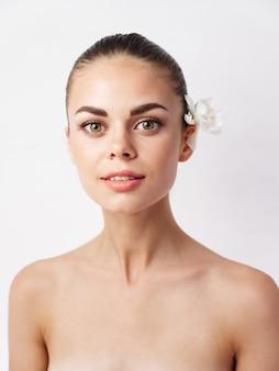 Mulher bonita com uma flor no cabelo, ombros nus, cosméticos, aparência atraente