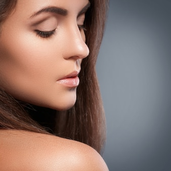 Mulher bonita com uma forma perfeita de sobrancelha e maquiagem nude