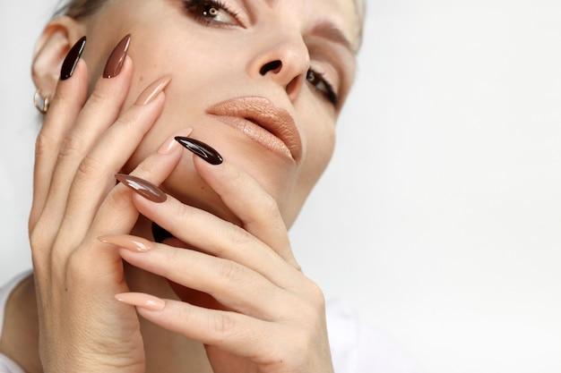 Mulher bonita com uma longa manicure coberta com tons naturais de esmalte