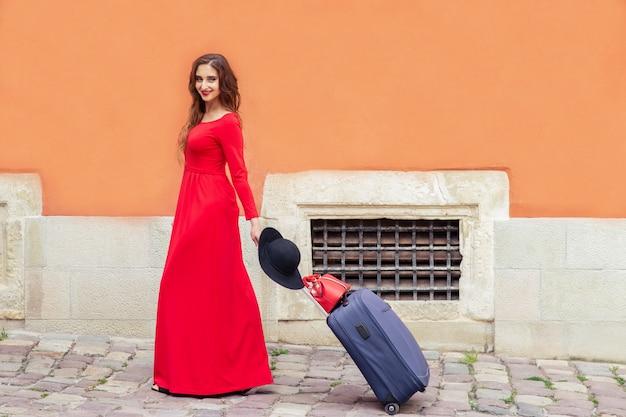 Mulher bonita com uma mala andando na cidade