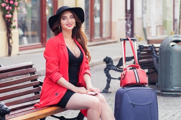 Mulher bonita com uma mala, sentado num banco