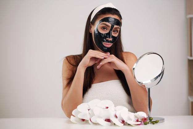 Mulher bonita com uma máscara preta de limpeza no rosto.