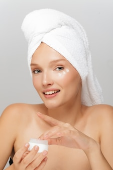 Mulher bonita com uma toalha branca e um frasco de creme