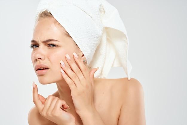 Mulher bonita com uma toalha na cabeça problemas de pele facial luz de fundo