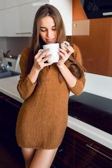 Mulher bonita com uma xícara de chá branca na cozinha moderna na hora da manhã ensolarada de outono.