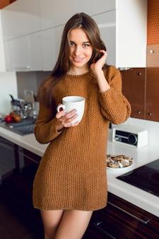 Mulher bonita com uma xícara de chá branca, olhando para fora da câmera na cozinha moderna na hora da manhã ensolarada de outono.