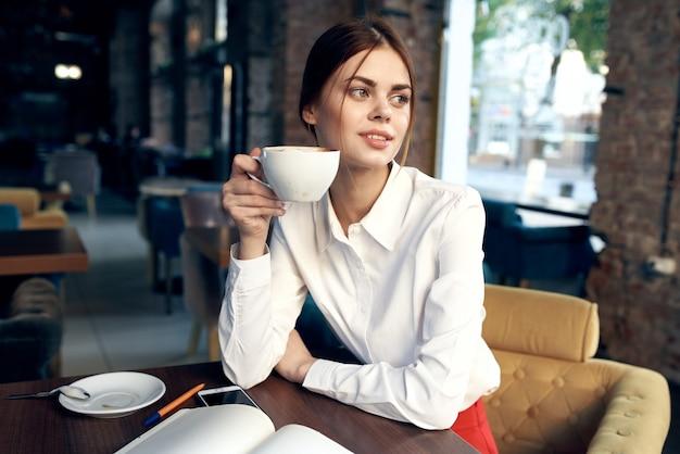 Mulher bonita com uma xícara na mão se senta à mesa em um café e faz uma reserva em um restaurante