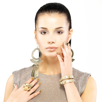 Mulher bonita com unhas de ouro e belas joias de ouro isoladas no fundo branco