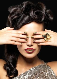 Mulher bonita com unhas douradas e batom criativo. modelo de garota morena com estilo de penteado na parede preta