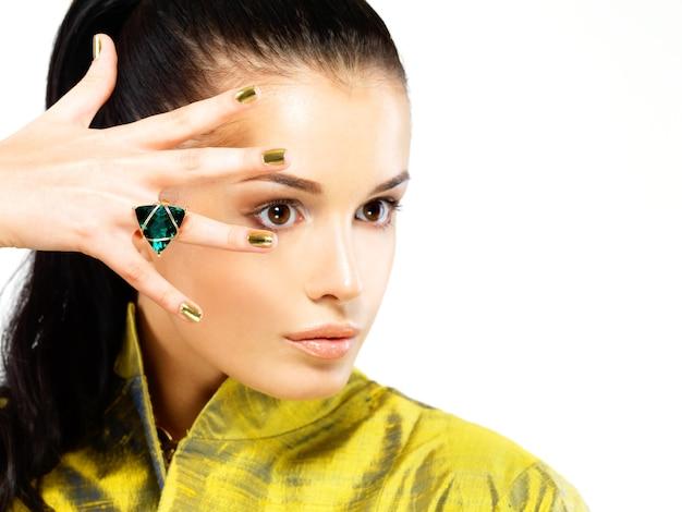 Mulher bonita com unhas douradas e esmeralda linda pedra preciosa - isolada no fundo branco
