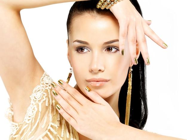 Mulher bonita com unhas douradas e joias de ouro lindas isoladas no branco
