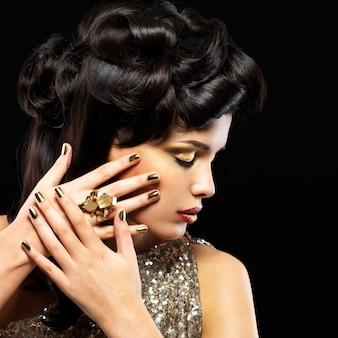Mulher bonita com unhas douradas e maquiagem fashion dos olhos. modelo de garota morena com estilo de penteado na parede preta