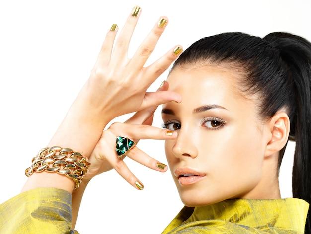 Mulher bonita com unhas douradas e uma linda pedra preciosa esmeralda