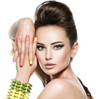 Mulher bonita com unhas multicoloridas e pulseira cravejada à mão