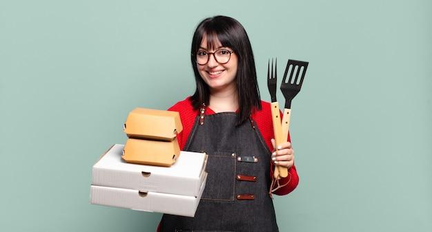 Mulher bonita com utensílios de cozinha e caixas para levar